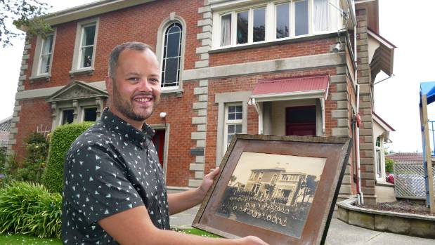St John's Girls' School deputy principal Nathan Hughes holding an old school photo taken in front of Gilmour House. The ...