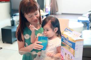A Chinese mother is shown serving Anmum to her daughter in this Fonterra publicity photograph.