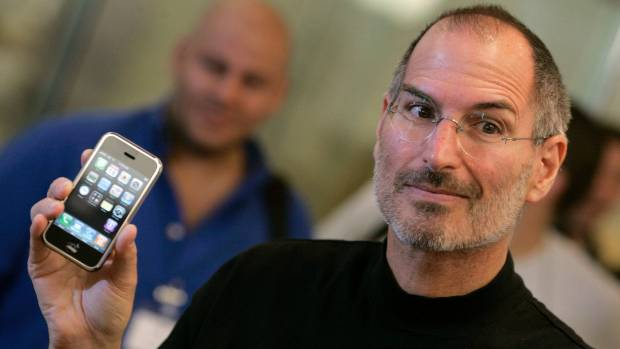 Steve Jobs holds the first iPhone which was released 10 years ago.