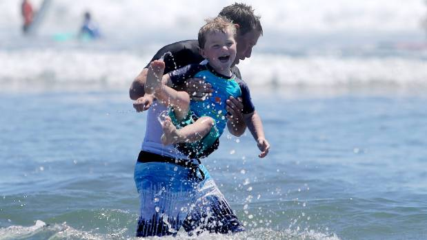 Chris Ashcroft and his son Adan, 3, from Kaponga, enjoy a swim at East End Beach in Taranaki.