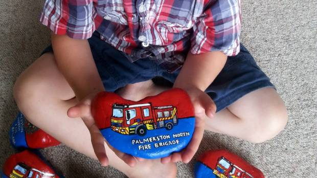 Toby Bateman, 3, with the Palmerston North Fire Brigade Palmy Rocks collection his mum Bronwyn painted.