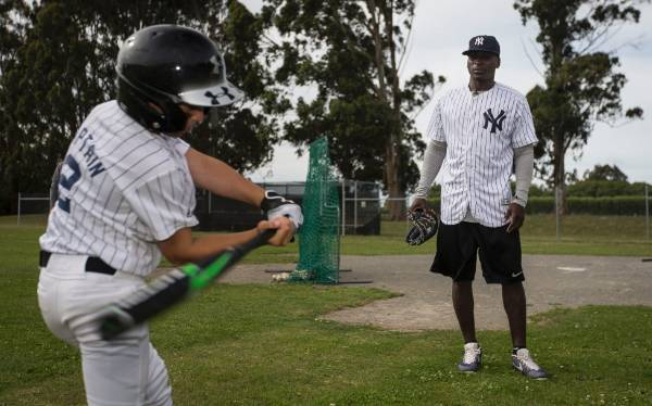 Didi Gregorius inspects the form of one of the junior players.