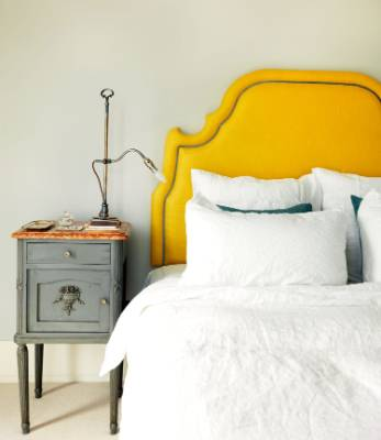 A yellow bedhead and French Louis XVI-style bedside table with marble top decorate this guest bedroom in a home in ...