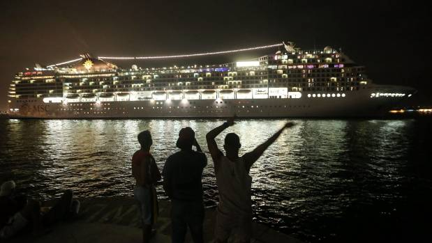 Brazilians wave as an Italian cruise ship departs from Rio's renovated port on December 8, 2016.