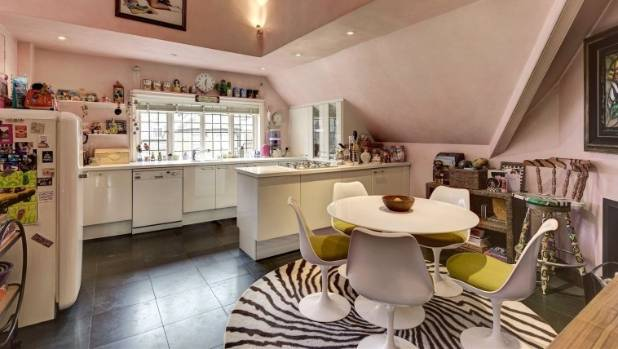 Pastel pink walls and animal print decor give the dining room and kitchen area a quirky vibe.