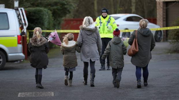 Young children arrive to leave floral tributes near the scene where seven-year-old Katie Rough was murdered.