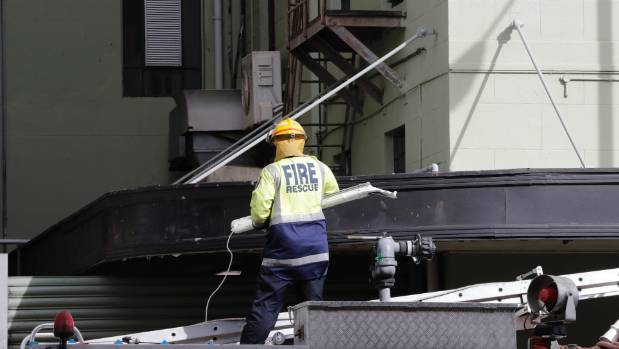 A fireman removes a fallen light from a damaged sign from the New Zealand Post building.