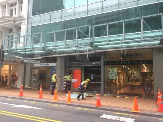 Firemen clear glass from Willis St in central Wellington after glass panel above fell and shattered on the street.