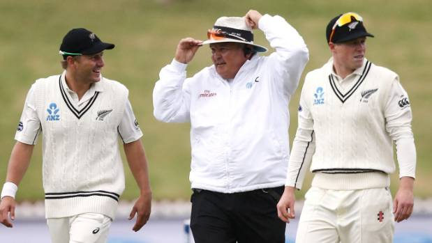 Umpire Marais Erasmus holds onto his hat much to the amusement of Neil Wagner.