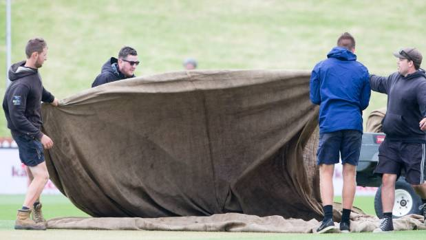 Basin Reserve ground staff had to battle the wind as they put covers on the pitch during a period of rain.