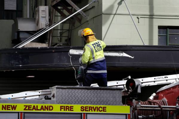 Fire officer removes a light that fell from the NZ Post billboard above.