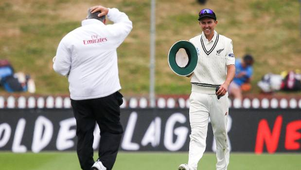 Trent Boult of New Zealand returns the hat of umpire Marais Erasmus of South Africa at a windswept Basin Reserve.