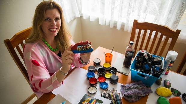 """Palmy Rocks painter Bronwyn Bateman working on a fire brigade """"Fire Rock"""" from her dining table """"studio""""."""