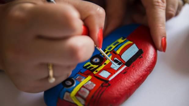 Artist Bronwyn Bateman applies detailing to a fire truck rock.