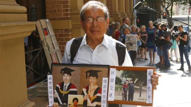 Kathy Lin's father Feng Qing Zhu holds up pictures of the deceased.