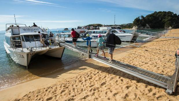 Passengers board a Wilson's tour boat in Kaiteriteri during a journey to Awaroa Bay in the Abel Tasman National Park.