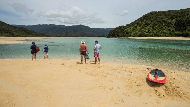 Visitors to Awaroa Bay in the Abel Tasman National Park, also known as New Zealand Beach, after a crowd-funding campaign ...