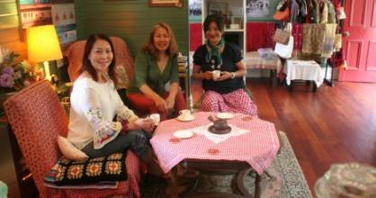 Offering a cuppa chai for travelers at the Paekakariki train station is Helen Keivom, right, with visitors Aymie David, ...
