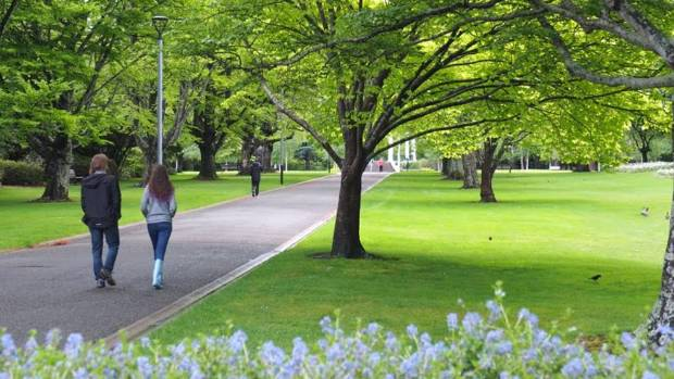 A couple take a stroll in Queen's Park.