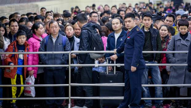 Passengers wait to enter a railway station during the annual Spring Festival travel rush in Guangzhou.