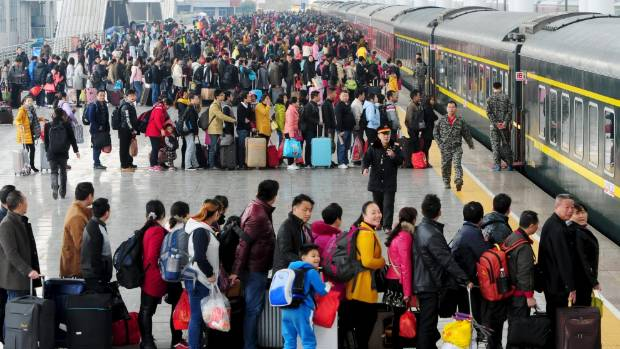 Passengers wait to board a train at a railway station during the Chinese Lunar New Year travel rush in Jiujiang.