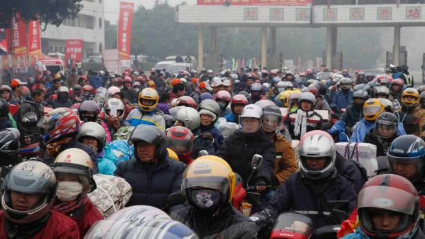 Migrant workers ride their motorcycles with families and friends on their way home for the Spring Festival, on a hazy ...