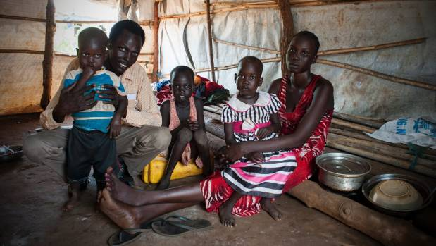 Nyajime Guet, 4, second from right, sits with her mother and father Michael, and siblings in their shelter at the ...