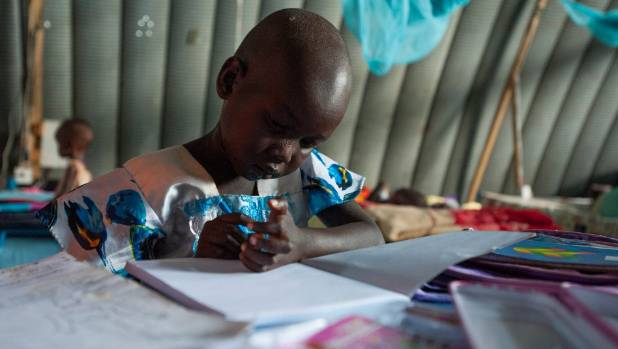 Nyajime Guet, 4, plays with pencils and paper given to her at the Mercy Corps hospital.