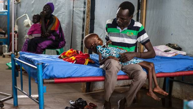 Nyajime Guet, 4, is held by her father Michael as he sits on a bed at a UNICEF-supported clinic.