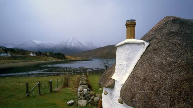 Traditional Scottish thatched cottage located on a river estuary surrounded by snow capped mountains, Isle of Skye, Scotland.