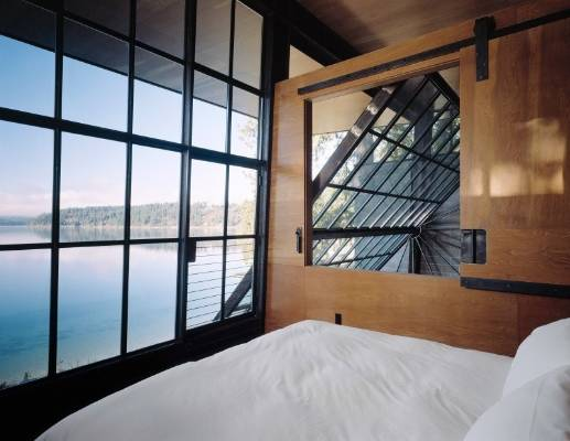 A sliding barn window opens up the master bedroom to the living area, while views are maximised by a large steel window.