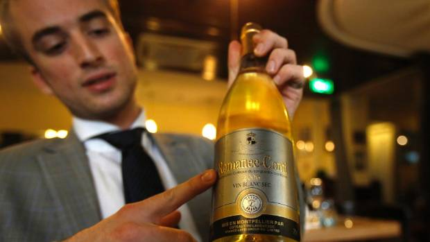 Charles Gaudfroy, a manager of a French restaurant, shows a bottle of fake Romanee-Conti, which was found at a wine shop ...
