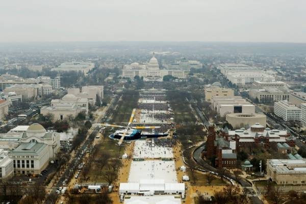 A helicopter flies above attendees as they line the Mall while partaking in the inauguration ceremonies to swear in ...