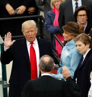 US President Donald Trump takes the oath of office with his wife Melania and son Barron at his side, during his ...