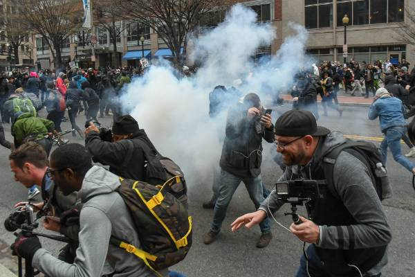 Protesters and journalists scramble as stun grenades are deployed by police during a protest near the inauguration.