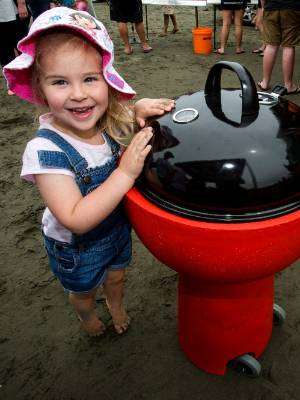 Isabelle Stock, 3, with the BBQ she won with the token she dug up.