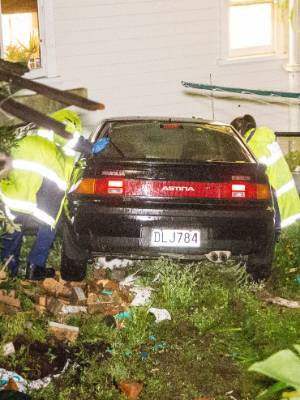 Police investigate the scene where a stolen vehicle was driven through a fence into a house in Cresent St, Richmond ...