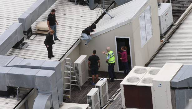The young woman joins police on the roof after talking with a police negotiator.
