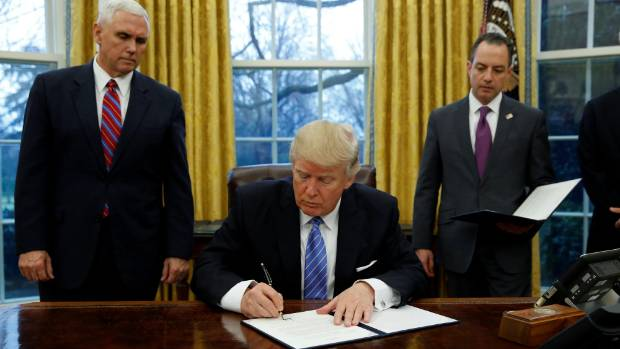 President Donald Trump signs an executive order on US withdrawal from the TPP, watched by Vice-President Mike Pence, ...