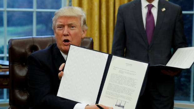 US President Donald Trump holds up the executive order on withdrawal from the Trans Pacific Partnership after signing it.