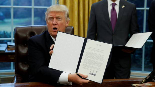 US President Donald Trump holds up the executive order on withdrawal from the Trans Pacific Partnership in the Oval Office.