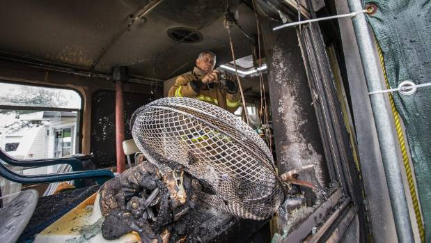 Nelson station officer Dick Lyall inspects the burnt interior of the motorhome at the Tahunanui Beach Motor Park.