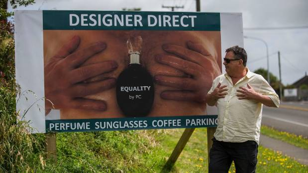 Designer Direct owner Michael Adams with his new billboard, featuring his own chest.