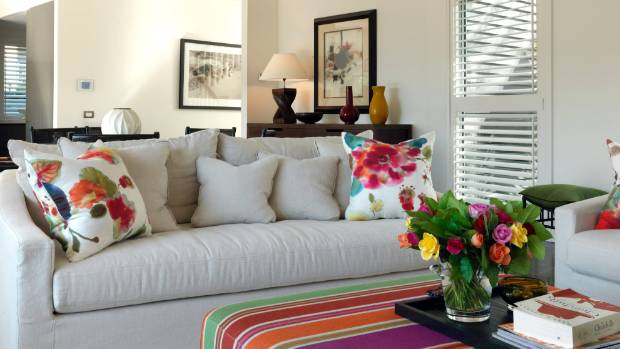 Bright linen cushions complement the ottoman in this stylish living room.