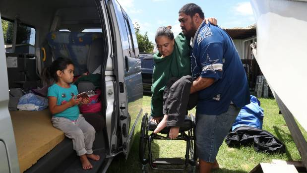 Tetriplegic Tracey Penny's partner Apera Wilson lifts her into the family's van, where they sleep alongside 4-year-old ...
