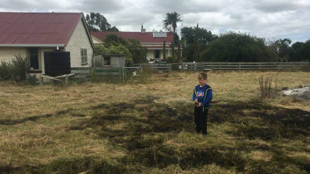 Hugo Smith, 6, in the blackened grass after helping put out the fire.