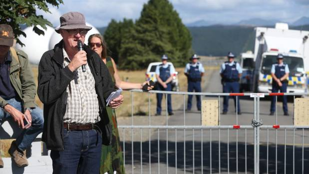 Anti Bases Campaign organiser Murray Horton addresses the crowd as police monitor the protest from inside the gates.