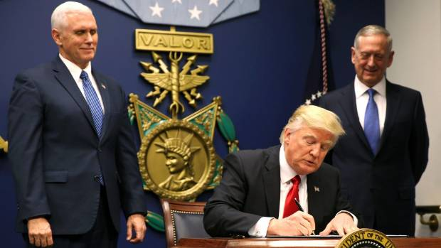 Mike Pence watches on as Donald Trump signs an Executive Order establising extreme vetting of people coming to the ...