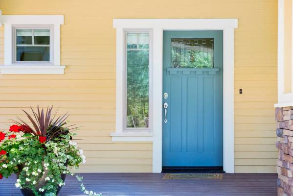 The buttery yellow of this homeu0027s painted exterior is the perfect companion for the blue of : doors nz - Pezcame.Com