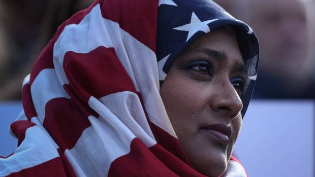 A woman wearing an American flag themed hijab listens to speakers during a protest against President Donald Trump's ...